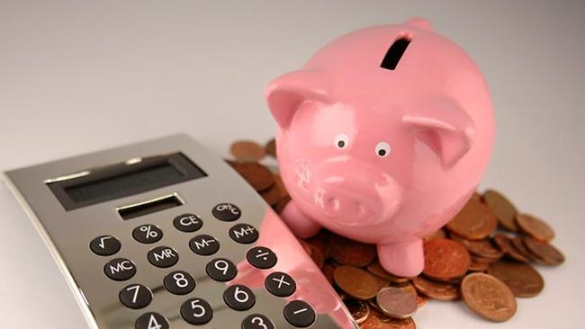 Piggy bank with calculator and some coins