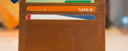 a brown wallet with three credit cards inside