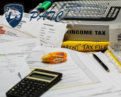 a closeup of calculator, highlighter, income tax textbooks and forms