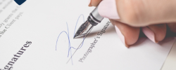 a close up of someone signing a contract with a nib pen
