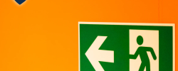 an emergency exit sign on an orange wall