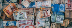 a wall with many countries' banknotes pinned to it