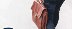 a person walking holding a brown leather bag