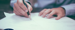 a close up photograph of a person signing a document